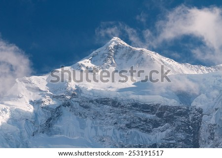 Snow-covered mountains in the area of Annapurna in the clouds under a bright blue sky