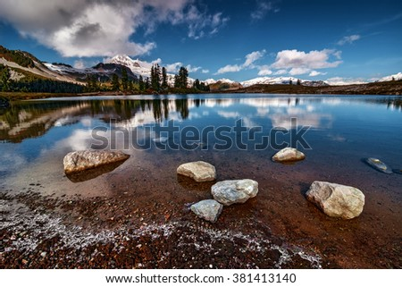 Snow covered mountains on the backdrop of a serene lake, rocks on the foreground - stock photo
