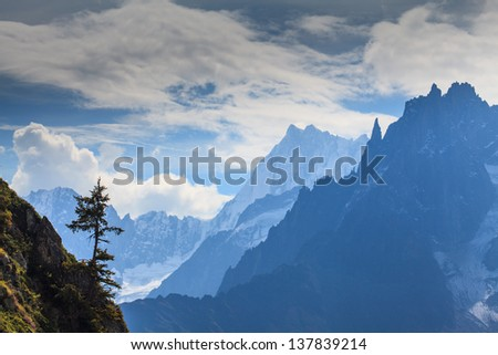 Snow covered mountains, rocky cliffs and an isolated pine tree in the French Alps - stock photo
