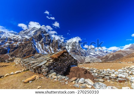Snow covered mountains, rocky peaks and stone lodge in Himalaya - stock photo