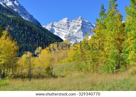 snow covered mountains with colorful yellow, green and red aspen during foliage season in Colorado