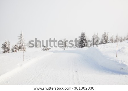 Snow covered norwegian road and landscape disapears in the mist - stock photo