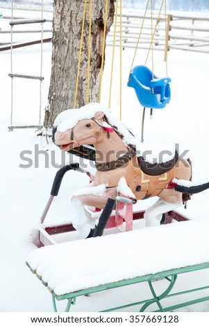 Snow covered outdoor swing, ladder and bouncy horse - stock photo