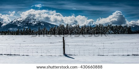 Snow Covered Peaks Pine Trees and farm fence Wyoming Winter Landscape  Hazelton Peak - stock photo