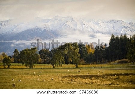 Snow covered peaks wrapped in cloud at sunrise, farmland in foreground