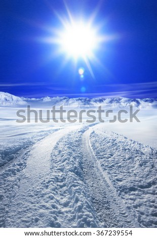 Snow covered road in winter with mountains in the distance - stock photo