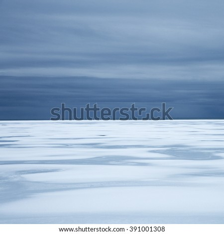 Snow covered sandur, starting to melt creating patterns under dramatic skies,  Southern Iceland - stock photo