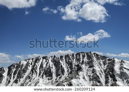 Snow covered sharp mountain ridge - stock photo