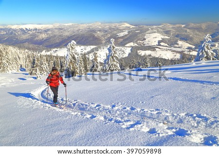 Snow covered slope and woman ascending on touring skis in sunny winter day - stock photo