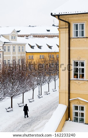 Snow covered square wth trees and walking man silhouette - stock photo