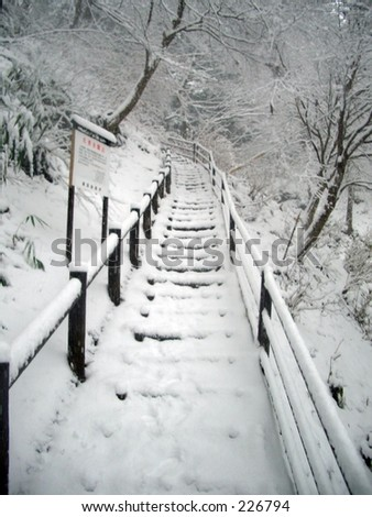 Snow covered steps leading up to the mountain top buddhist temple of Mt. Takao, outside of Tokyo, Japan. - stock photo
