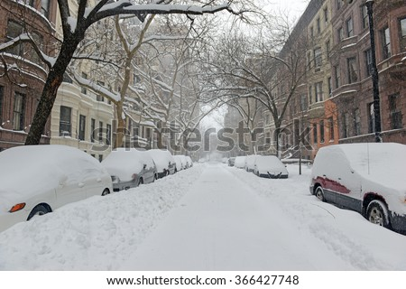 Snow covered street and Brownstone buildings during snowstorm in Manhattan, New York City - stock photo