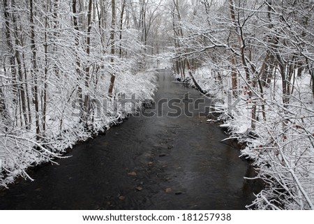Snow Covered Trees Framing A Little Stream During Winter In The Park, Sharon Creek At Sharon Woods, Southwestern Ohio, USA - stock photo