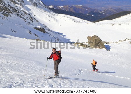 Snow covered valley and a couple of ski mountaineers ascending in sunny winter day - stock photo