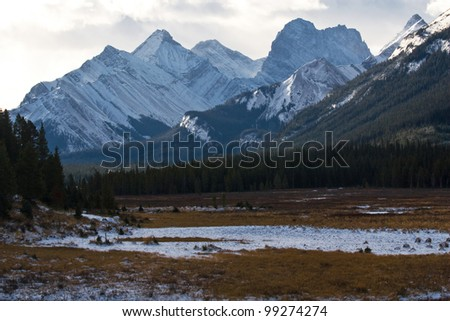 Snow covered valley with rockies on background - stock photo