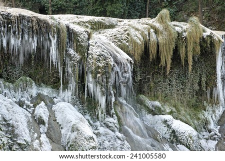 Snow covered waterfall with ice stalactites - stock photo