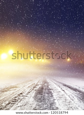 Snow covered winter road with shining streetlights at night - stock photo