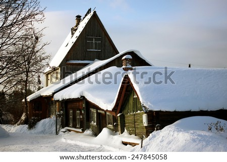 snow-covered wooden houses in winter village - stock photo