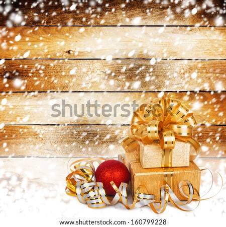 Snow-covered wooden wall with a beautiful gift box and bow - stock photo
