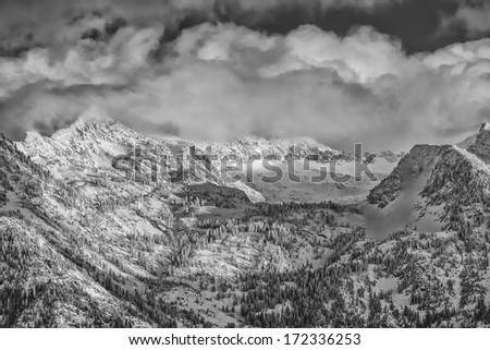 Snow covers the Wasatch mountains in January 2014 with clouds hanging over them low. shot taken from the Salt Lake city Valley in Utah USA in BW/ Wasatch mountains in Winter
