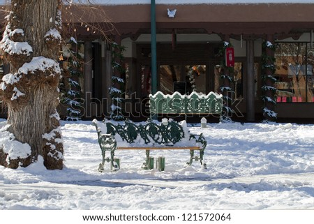 Snow covers two benches in Santa Fe's historic Plaza - stock photo