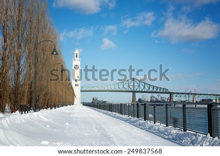Snow drifts across the path to the Tour de l'Horloge, Montreal Clock Tower, with the Jaques Cartier Bridge in the background. In Old Port, Montreal Quebec, Canada - stock photo