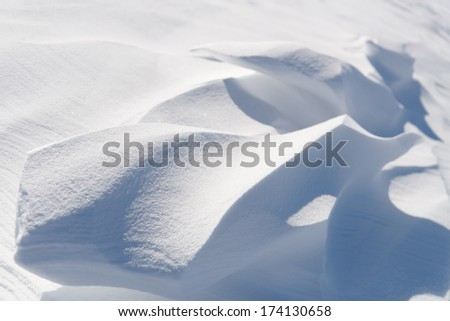 Snow drifts in the sunlight.