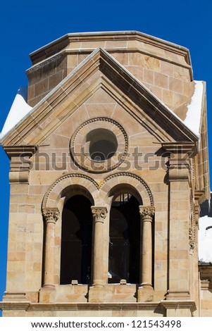 Snow enhances a tower on Santa Fe's beautiful St. Francis Cathedral and Basilica - stock photo