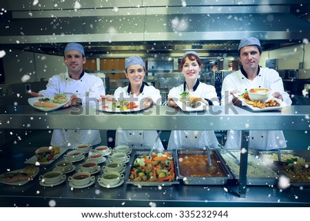 Snow falling against four young chefs showing plates - stock photo
