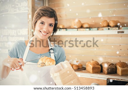 Snow falling against pretty waitress picking up croissant