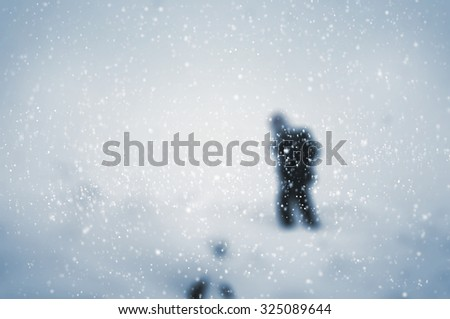 Snow falling against winter landscape with a lone hiker - focus on snowflakes - stock photo