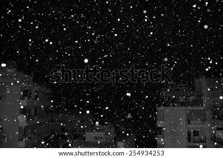 Snow falling over city buildings at night. Black and white.