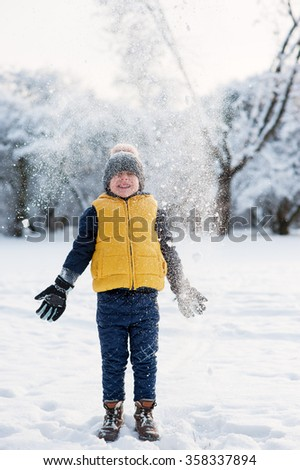 Snow falls on the boy near forest