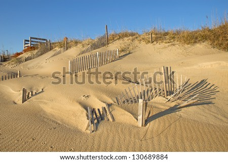 Snow fencing helps stabilize the dune line at a beach in Nags Head, North Carolina, after the ravages of recent storms including Hurricane Sandy - stock photo