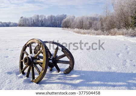 Snow frost covered field with two antique wooden wheels by the forest - stock photo
