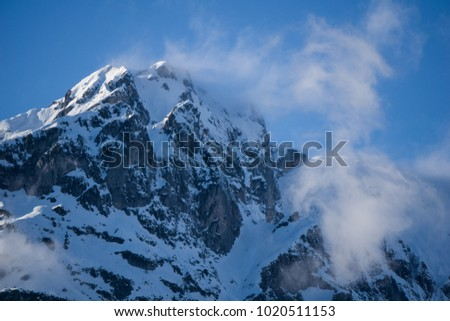 Snow getting blown off the top of a mountain due to gusts of wind