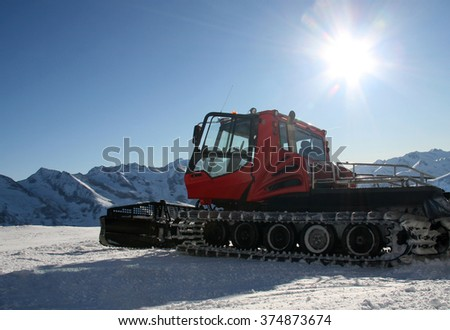 Snow-grooming machine on snow hill ready for skiing slope preparations in Austrian Alps.