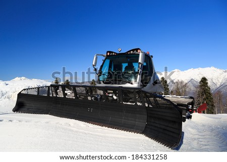 Snow-grooming machine on snow hill ready for skiing slope preparations in Russian Krasnaya Polyana - stock photo