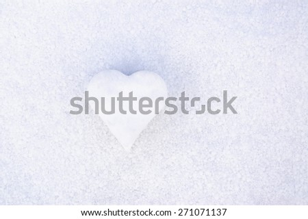 Snow heart. Heart shaped from snow on snowy background.
