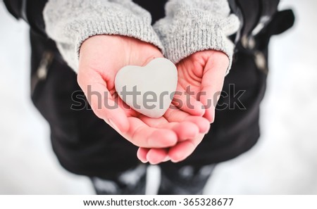Snow heart in hands. Saint Valentine's day concept