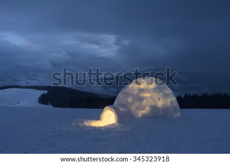 Snow igloo. Winter in the mountains. Evening Landscape with shelter for extreme tourists. Adventure Outdoors - stock photo