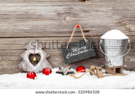 Snow in a bucket on a sled, on wooden background, with Christmas decoration - stock photo