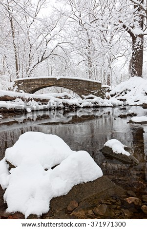 Snow kissed trees and boulders surround a stone bridge that crosses the dark water of a tranquil winter stream.