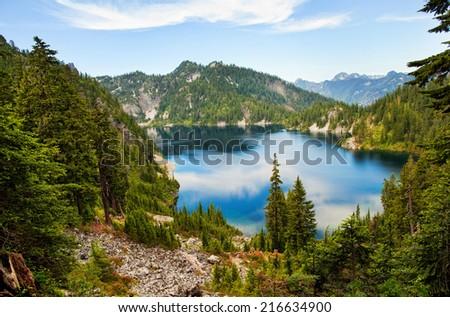 Snow lake in summer, Washington, mountains, water reflection, USA - stock photo