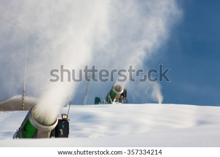 Snow-machine bursting artificial snow  over a skiing slope to alow for the skiing season to start - stock photo
