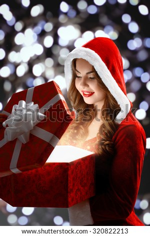 Snow Maiden in red suit smiling holding a gift, opens a gift; on a dark background, portrait.