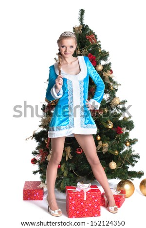 Snow Maiden posing with Christmas tree and gifts - stock photo