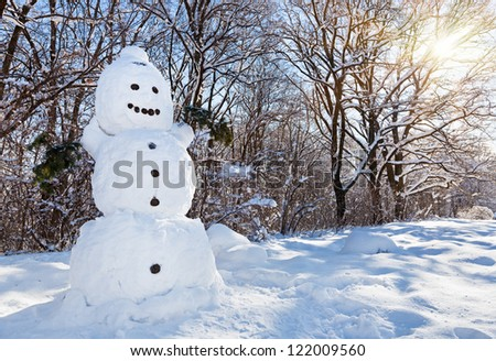 Snow man in winter forest covered by hard snow and bright sun - stock photo