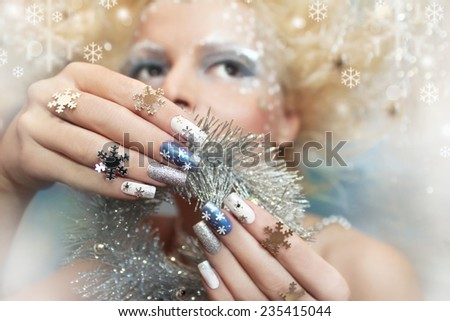 Snow manicure on colored nail Polish with silver snowflakes on the girl. - stock photo