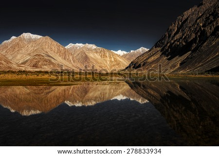 snow mountain range and reflection. Filtered :cross processed vintage effect. Ladakh ,India - stock photo